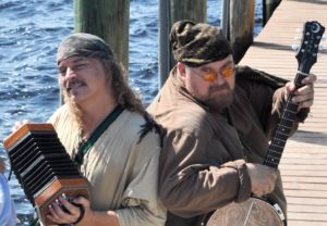 Two men dressed in pirate garb holding musical instruments.