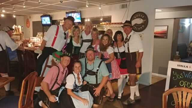 Group of people dressed in traditional German garb posing for a photo at South Beach Grille during the Tapa Hop.
