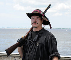 Man dressed in pirate garb with a rifle over his shoulder.