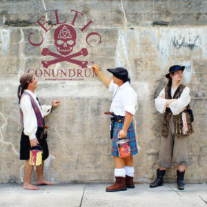Three men in pirate garb. The words Celtic Conundrum are on the wall.