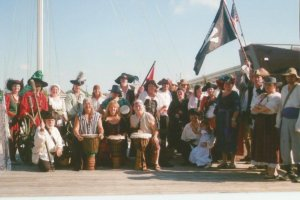 Large group of people dressed in pirate garb and posing for a group photo.