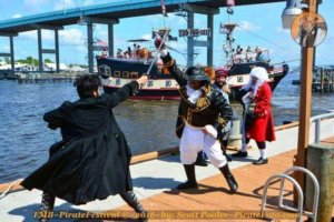 Two men in pirate garb swordfighting. Others look on and a pirate ship is in the background.