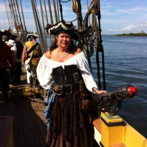 Woman in pirate garb on a pirate ship standing next to a cannon. Other pirates can be seen in the background.
