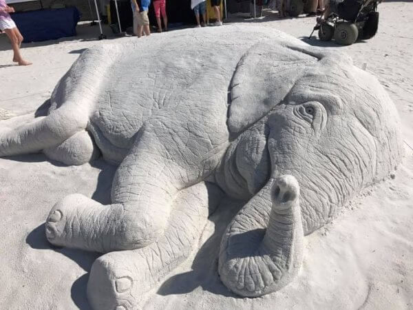 Sand sculpture of an elephant lying on its side.