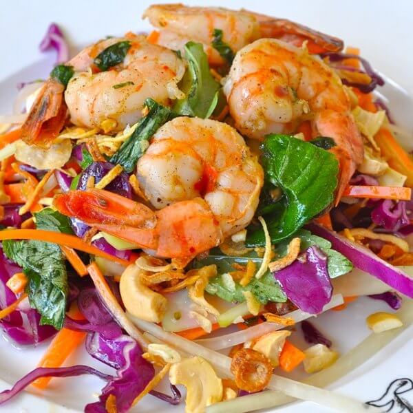 A tasty looking plate of boiled shrimp on top of a bed of salad.
