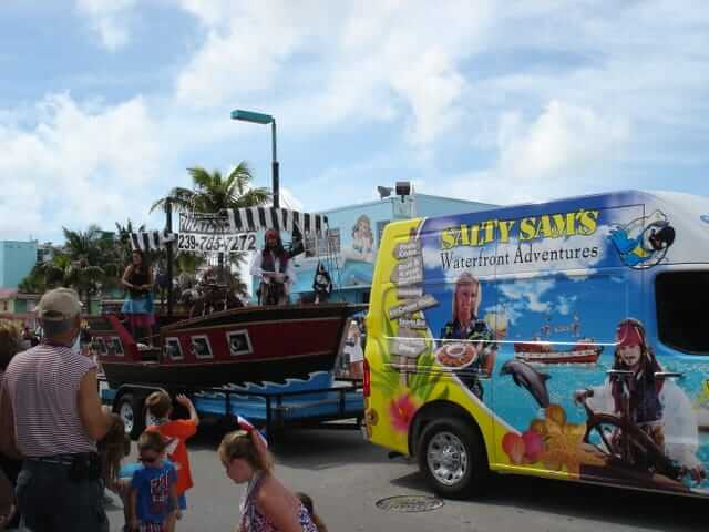 The Salty Sam's float in the Fort Myers Beach Fourth of July Parade. Their advertising wrapped passenger van is pulling a replica of the Salty Sam's Pirate Ship.