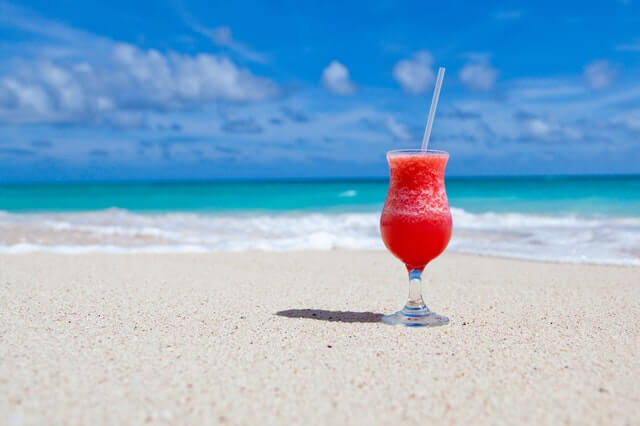 Image of a red slushy cocktail on the sand with the ocean in the background.