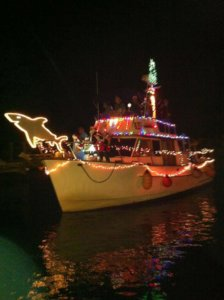 Boat decorated with Christmas lights. Partygoers can be seen in Christmas attire. There is a lit up shark on the bow.
