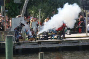 Group of people on a dock dressed in pirate garb and firing a cannon.
