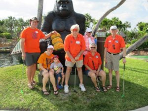 Team of mini golfers dressed in orange t-shirts posing with a gorilla statue.