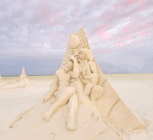Sand sculpture of a man and a woman seated together. A beautiful sunset is in the background.