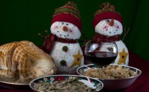 Plates of Christmas dishes and two stuffed snowmen.