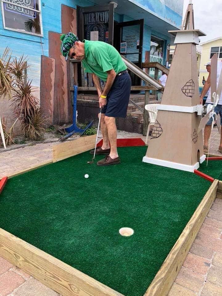 Man putting a golf ball on a miniature golf hole.