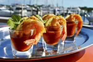 Three shots glasses filled with cocktail sauce and shrimp.