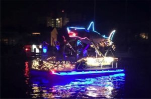 A pontoon boat decorated with a large shark and Christmas lights.