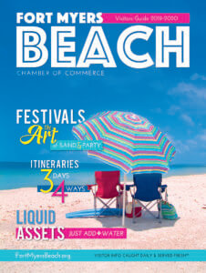 A magazine cover with an umbrella and chairs on the beach