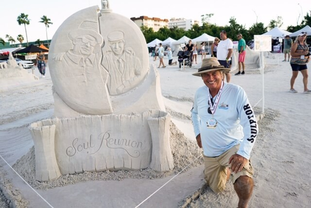 A sand sculptor kneels proudly next to his winning sand sculpture at the the American Sand Sculpting Championship on Fort Myers Beach.