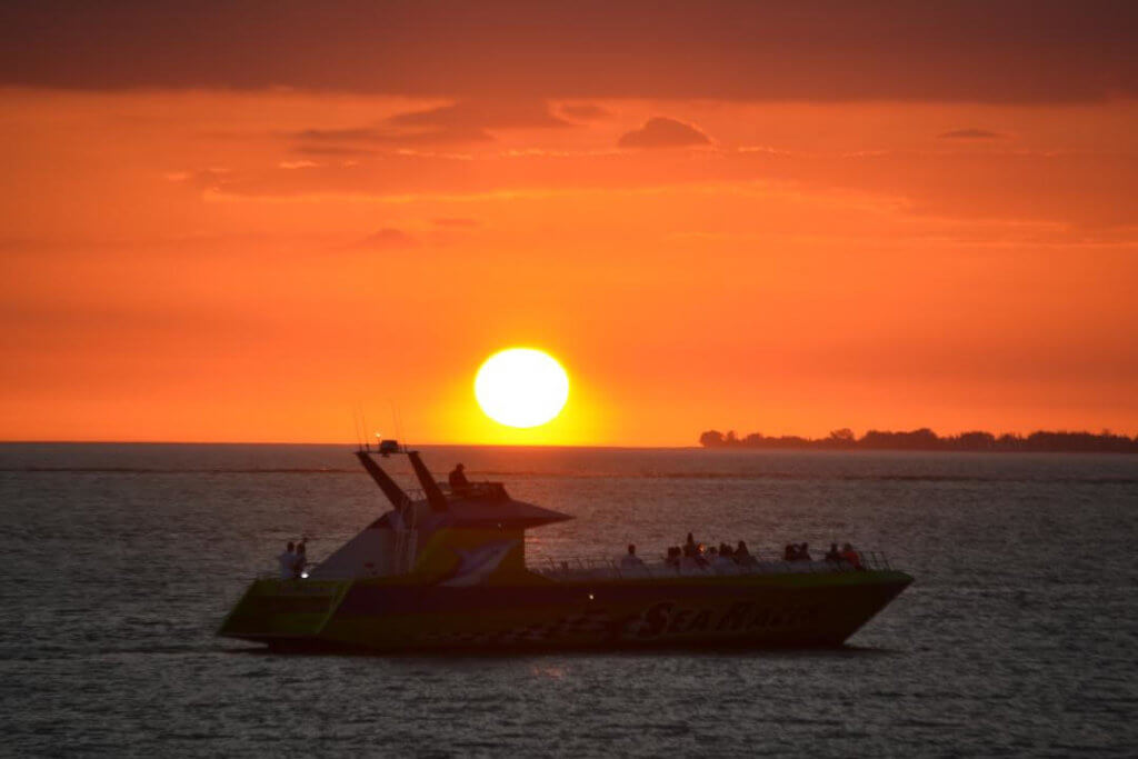 A jet boat full of passengers enjoys a view of the setting sun.