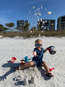 A child enjoys playing in the sand on Fort Myers Beach.