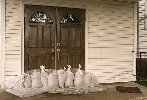 A front door is barricaded with sandbags in preparation for a flood.