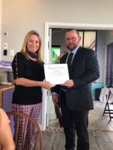 Lee County Sheriff Ryan Justham receives the FMB Chamber Deputy of the Month award from Jacki Liszak.